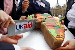 Slicing up Africa: Activists cut into an African-shaped cake outside of the British government's Department for International Development (DFID) to protest DFID's role in facilitating the acquisition of African land by large multinational conglomerates. Photo courtesy Global Justice Now/Flickr