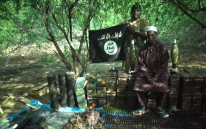 A Boko Haram militant speaks to the camera while sitting atop boxes of stolen ammunition after an assault on a Nigerian military position. Photo a screenshot of Boko Haram video courtesy Aaron Y. Zelin/jihadology.net